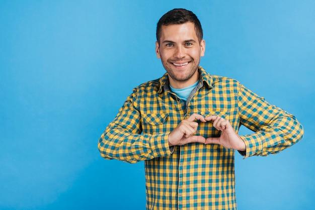 Homem feliz fazendo um coração com os dedos