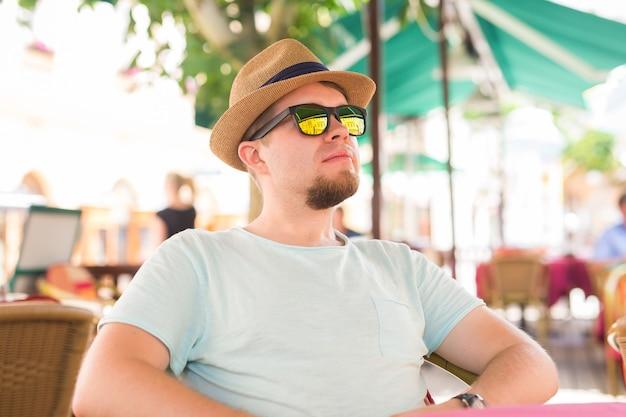 Homem feliz fazendo uma pausa para o café no café ao ar livre durante um bom dia de verão.