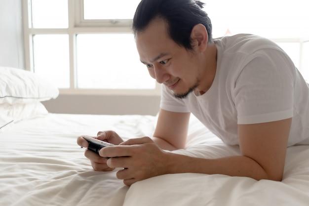 Homem feliz fica em casa e joga jogo móvel em seu apartamento.