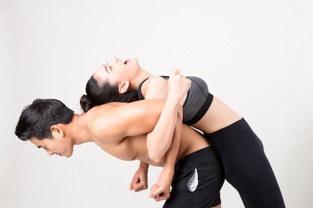 Homem feliz fitness jovem carregando sua namorada após o treino. fitness e estilo de vida saudável.