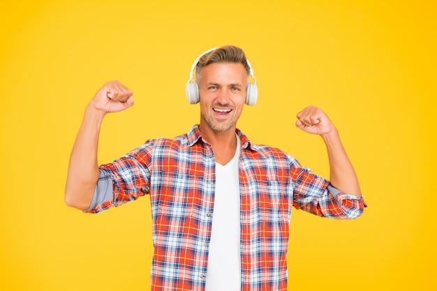 Homem feliz flexionar os braços fortes, ouvindo música em fundo amarelo de fones de ouvido modernos, potência de som.