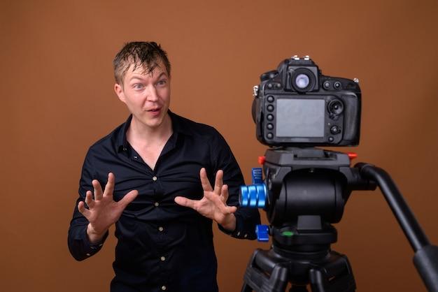 Homem feliz influenciador vlogging com câmera dslr