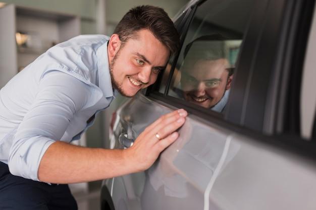 Homem feliz, inspecionando seu carro novo