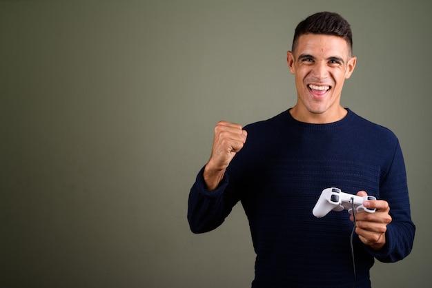 Homem feliz jogando videogame com controlador de jogo contra um fundo colorido