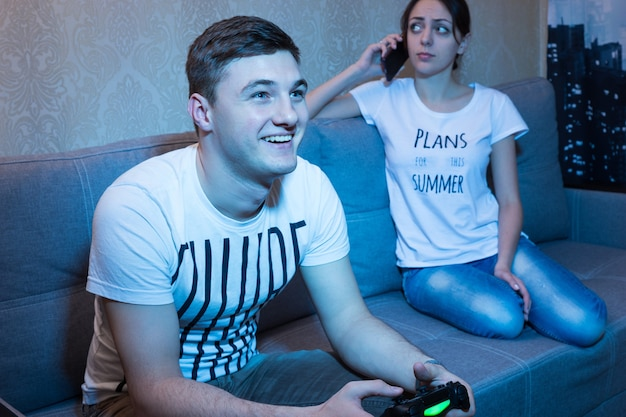 Homem feliz jogando videogame com um sorriso radiante de prazer sentado no sofá em casa enquanto sua namorada falando ao telefone decepcionada com seu comportamento