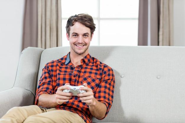 Homem feliz jogando videogame no sofá