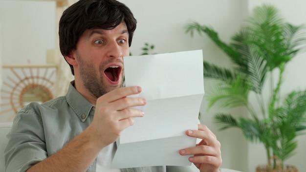 Homem feliz lê uma carta, recebe notícias agradáveis.