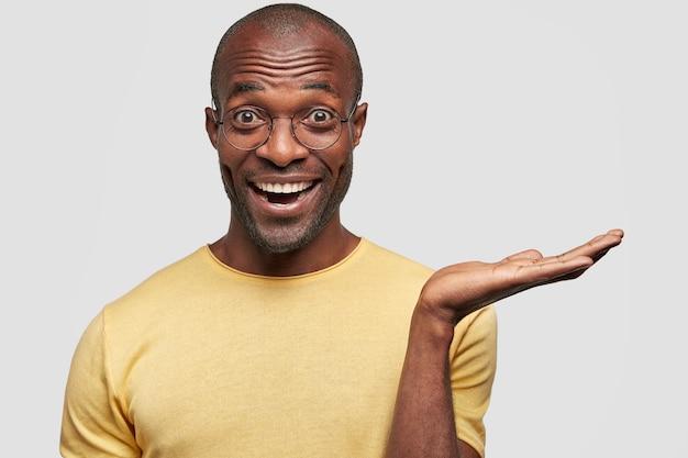 Homem feliz levanta a palma da mão como se segurasse algo, olha alegre, demonstra algo aos clientes