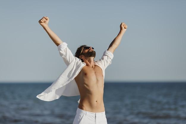 Homem feliz levantando os braços em uma camisa branca na praia