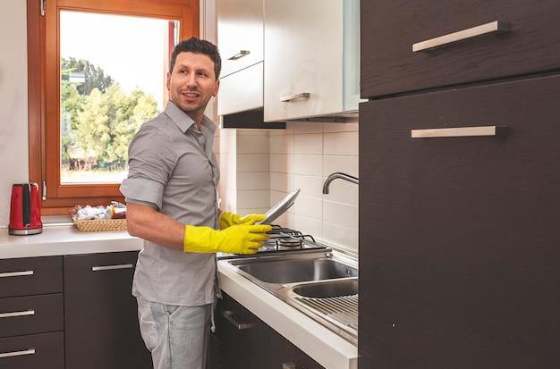Homem feliz limpa a louça em casa.