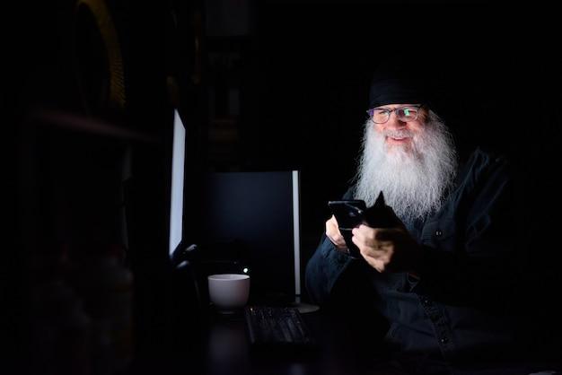 Homem feliz maduro barbudo hippie usando o telefone enquanto trabalhava horas extras em casa no escuro