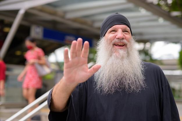 Homem feliz maduro bonito barbudo acenando com a mão do lado de fora da estação de trem do metrô