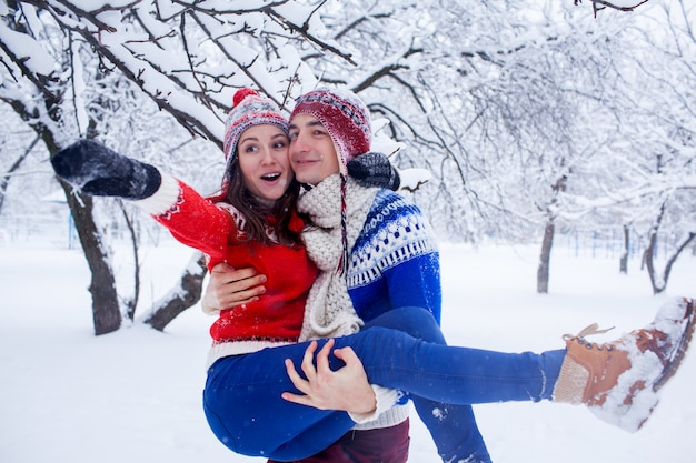 Homem feliz mantém sua namorada nos braços na floresta de inverno