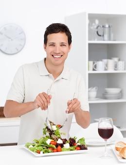 Homem feliz, misturando uma salada em pé na cozinha