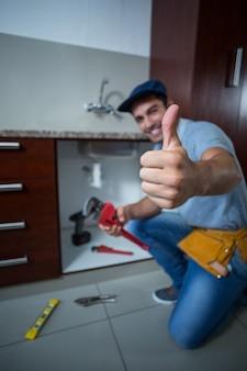 Homem feliz, mostrando os polegares, mantendo a chave inglesa