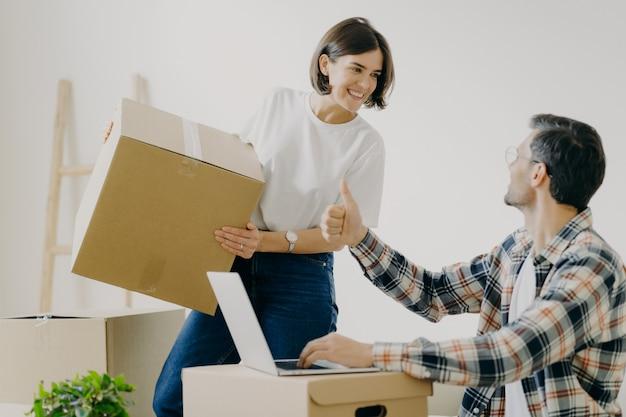 Homem feliz na camisa quadriculada mostra como gesto, fazer planos com a esposa sobre casa nova