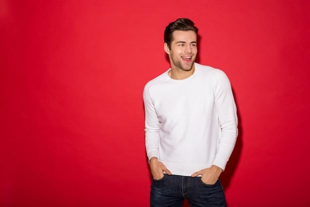 Homem feliz na camisola, olhando para longe com os braços nos bolsos sobre parede vermelha
