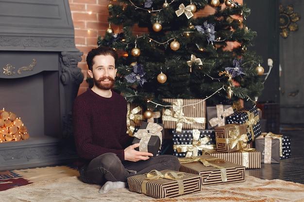 Homem feliz na camisola vermelha. cara em frente à lareira. macho no fundo da árvore de natal.