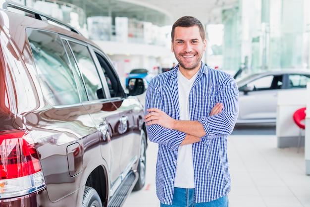 Homem feliz na concessionária de carros