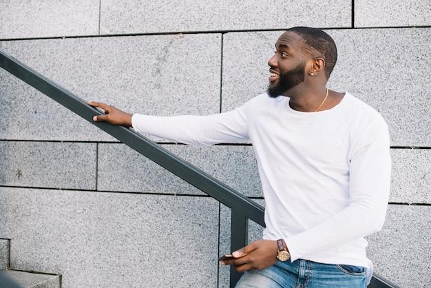 Homem feliz na escada olhando para cima