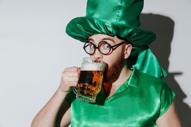 Homem feliz na fantasia de st.patriks bebendo cerveja