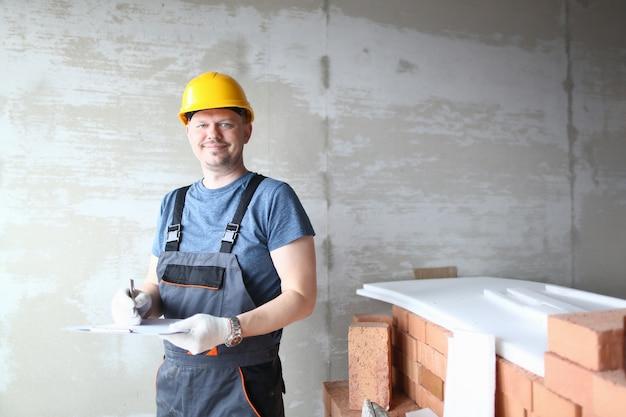 Homem feliz no capacete amarelo, aproveitando o trabalho em construção