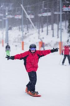 Homem feliz no casaco vermelho no snowboard skiin na montanha. está nevando
