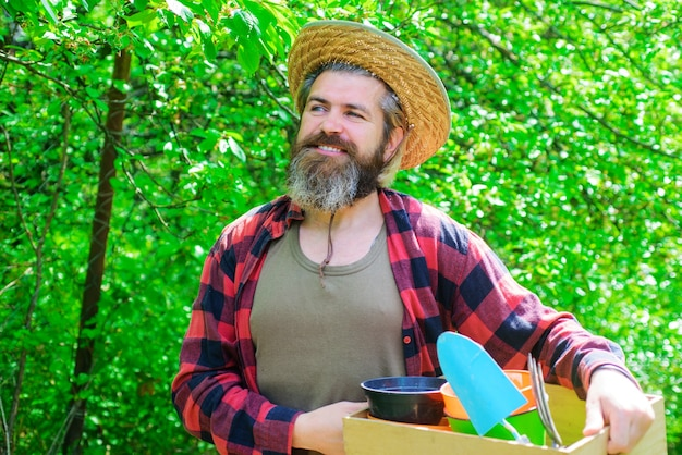 Homem feliz no jardim primavera. jardineiro na fazenda eco com plantio de ferramentas de jardinagem.