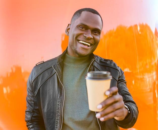 Homem feliz no meio do tiro segurando café e esperando pelo caminhão de comida