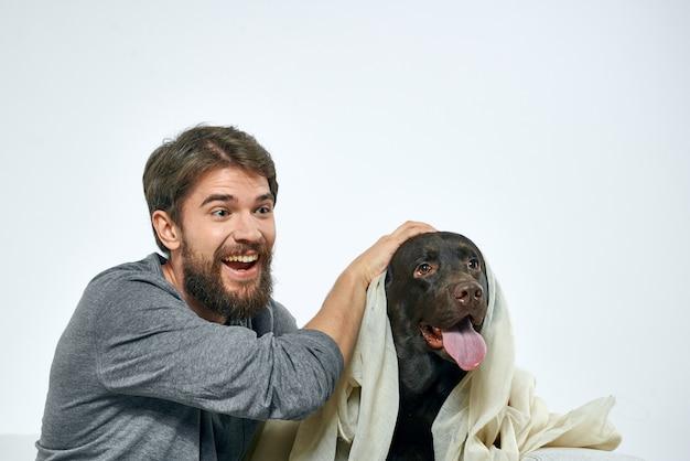 Homem feliz no sofá com seu cachorro, isolamento e quarentena com cachorro em casa