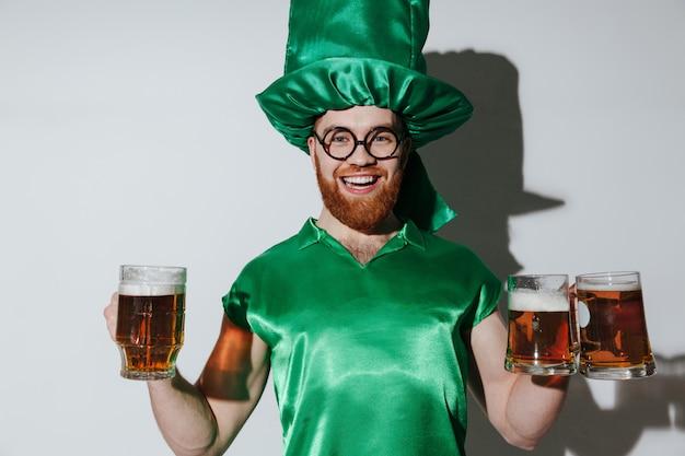 Homem feliz no traje de st.patriks segurando copos