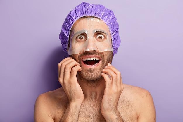 Homem feliz nu aplica máscara hidratante no rosto, usa touca de banho violeta, gosta de tratamento cosmético para a pele, tem olhos castanhos esbugalhados, ombros nus