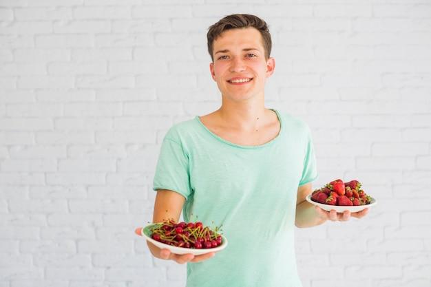 Homem feliz, oferecendo, prato, cerejas, e, morangos