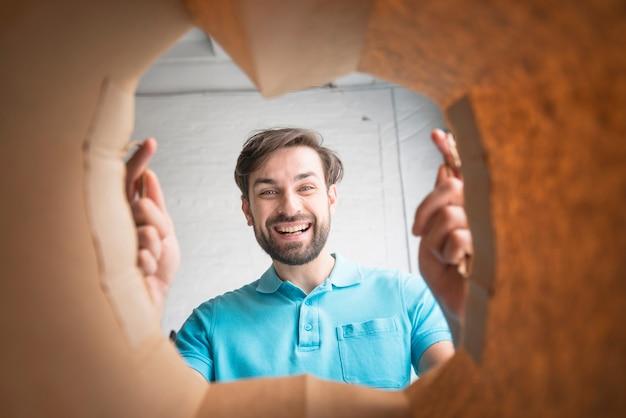 Homem feliz olhando dentro do saco de papel