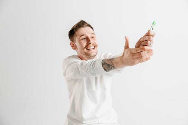 Homem feliz olhando para o teste de gravidez no estúdio.