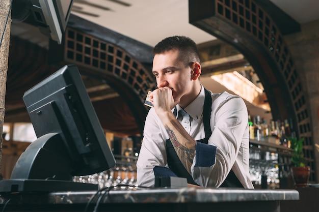 Homem feliz ou garçom no avental no balcão com caixa trabalhando no bar ou cafeteria