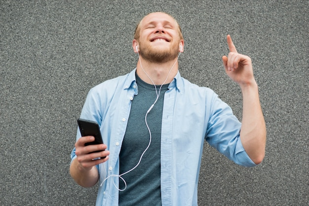 Homem feliz ouvindo música em fones de ouvido