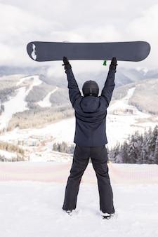 Homem feliz parado com uma prancha de snowboard na cabeça no topo de uma colina