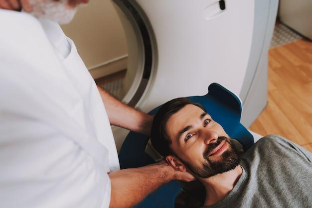 Homem feliz, passando por exame de ressonância magnética aberta na clínica.