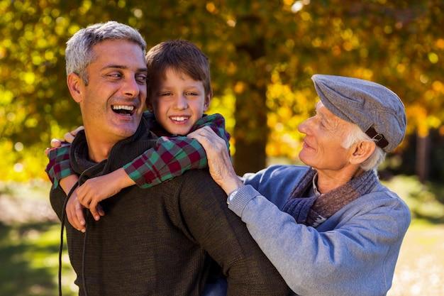 Homem feliz, pegando carona filho enquanto com o pai no parque