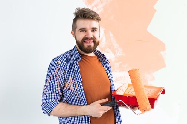 Homem feliz pintando a parede em seu novo apartamento. conceito de renovação, redecoração e reparação.