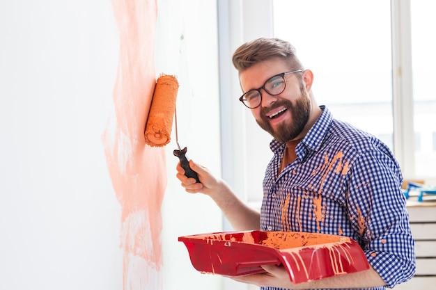 Homem feliz pintando a parede interior da casa. conceito de renovação, reparação e redecoração.