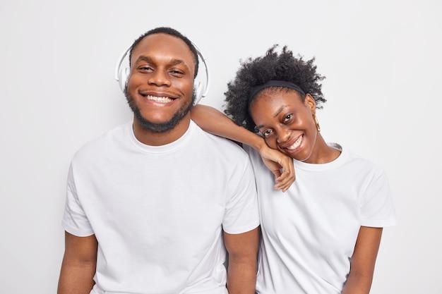 Homem feliz por passar o tempo livre juntos sorrir agradavelmente vestido casualmente ouvir música em fones de ouvido isolados no branco