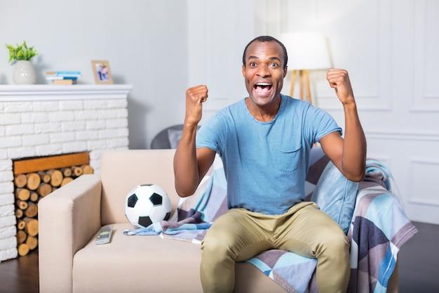 Homem feliz, positivo e simpático, sentado no sofá e animado enquanto assiste a uma partida de futebol