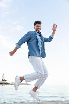 Homem feliz pulando ao ar livre