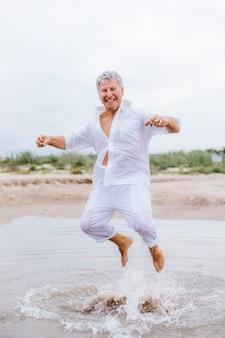 Homem feliz pulando na praia