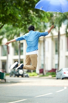 Homem feliz pulando na rua