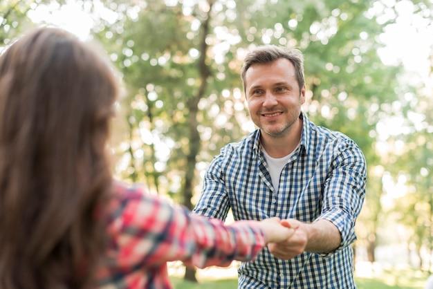 Homem feliz, puxando sua filha e brincando no parque