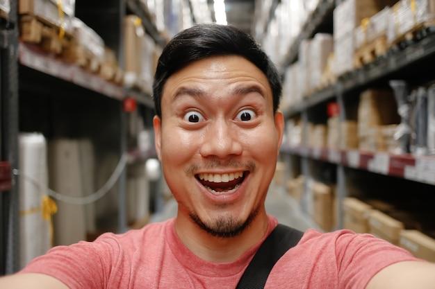 Homem feliz que compra no armazém.