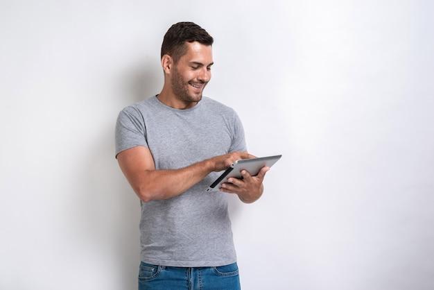 Homem feliz que está com o ipad que olha a tela dele.